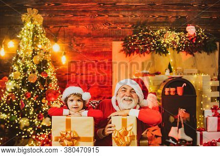 Family Holiday. Little Santa Grandfather And Grandson With Bag - Delivery Christmas Gift. Santa Help