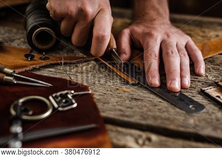 Close Up Of A Shoemaker Or Artisan Worker Hands. Leather Craft Tools On Old Wood Table. Leather Craf