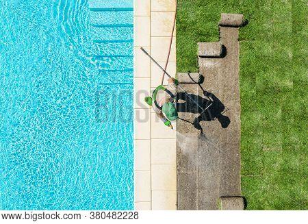 Professional Caucasian Gardener In His 40s Finishing Lawn Around Swimming Pool Installing New Grass