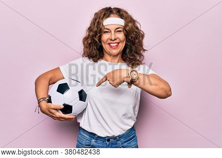 Middle age beautiful sporty woman playing soccer holding football bal over pink background smiling happy pointing with hand and finger