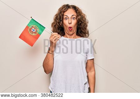 Middle age beautiful patriotic woman holding portuguese flag over isolated white background scared and amazed with open mouth for surprise, disbelief face