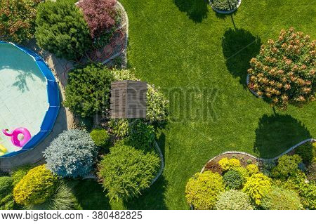 Gardening And Landscaping Industry. Residential Backyard Garden With Small Swimming Pool From Above