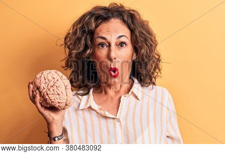 Middle age brunette woman asking for care memory holding brain over yellow background scared and amazed with open mouth for surprise, disbelief face