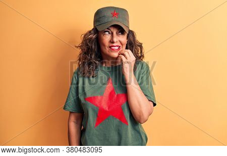 Middle age brunette woman wearing t-shirt and cap with red star symbol of communism thinking concentrated about doubt with finger on chin and looking up wondering