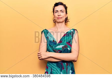 Young beautiful hispanic woman wearing casual dress skeptic and nervous, disapproving expression on face with crossed arms. negative person.