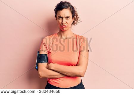 Young beautiful hispanic woman wearing sportswear using smartphone skeptic and nervous, disapproving expression on face with crossed arms. negative person.