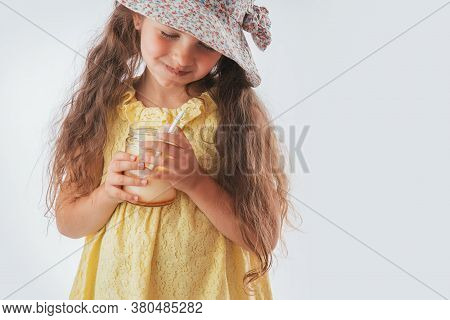 Beautiful Little Girl With Spoon In Mouth Eating Tasty Cream. Eating Yummy Ice Cream Is Fun