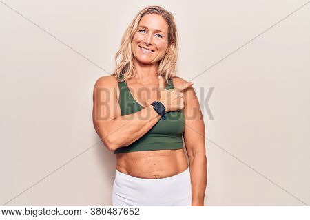 Middle age caucasian blonde woman wearing sportswear cheerful with a smile of face pointing with hand and finger up to the side with happy and natural expression on face