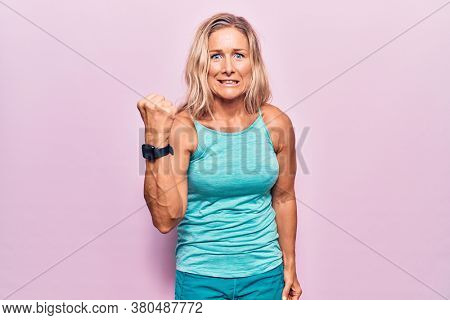 Middle age caucasian blonde woman wearing sports clothes over pink background angry and mad raising fist frustrated and furious while shouting with anger. rage and aggressive concept.