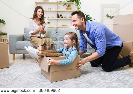 Family Relocation Concept. Dad Riding Little Daughter In Moving Box Having Fun In New Home. Selectiv