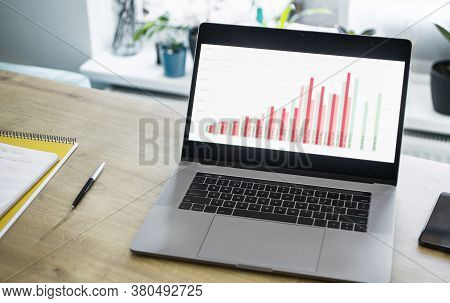 Open Laptop With Business Charts On The Table In The Home Office Remote Worker Concept