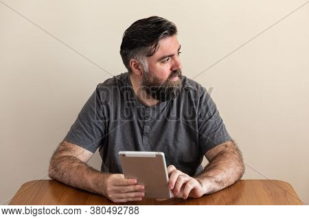 Caucasian Man With A Beard And Gray Hair, Gray Shirt, With A Tablet In His Hands On A Table. He's Si