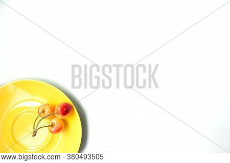 Sweet Cherry In A Yellow Plate. Ripe Sweet Cherries On A Yellow Plate On A White Fabric Background.