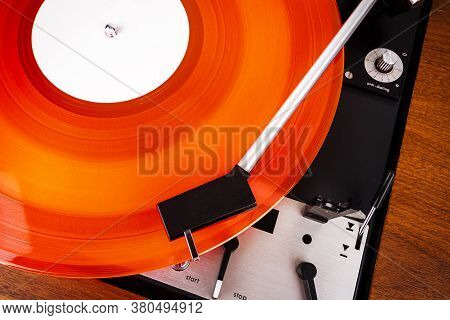 Close Up Of Turntable Needle On A Vinyl Record. Turntable Playing Vinyl. Needle On Rotating Red Viny