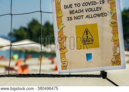 Chalkidiki, Greece - July 30 2020: Covid-19 Beach Volley Is Not Allowed Sign. Day View Of Paper Info