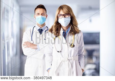 Shot Of Female And Male Doctors Standing Together On The Clinic's Foyer While Looking At Camera. Med