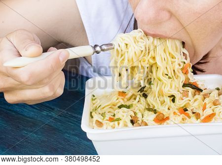 A Girl Eats Instant Noodles With A Fork From A Container. Closeup. Junk Food. Fastfood