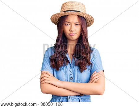 Young beautiful chinese girl wearing summer hat skeptic and nervous, disapproving expression on face with crossed arms. negative person.