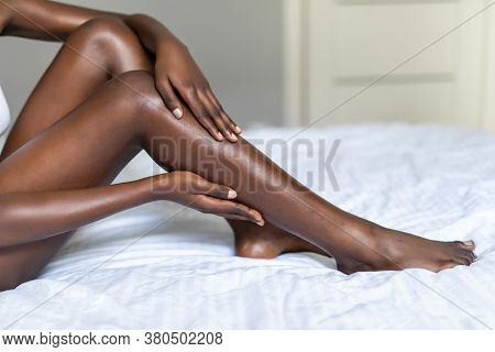 Close Up Of Young Dark Skin Woman With Perfect Body Touching Gently Her Hairless Soft And Silky Legs