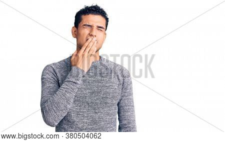 Hispanic handsome young man wearing casual sweater bored yawning tired covering mouth with hand. restless and sleepiness.
