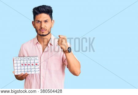 Handsome latin american young man holding heart calendar annoyed and frustrated shouting with anger, yelling crazy with anger and hand raised
