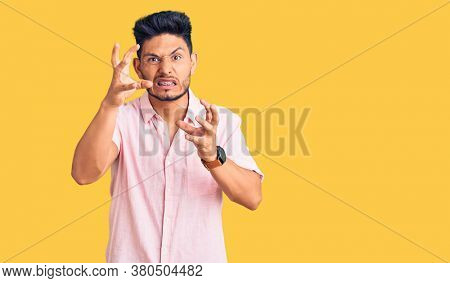 Handsome latin american young man wearing casual summer shirt shouting frustrated with rage, hands trying to strangle, yelling mad