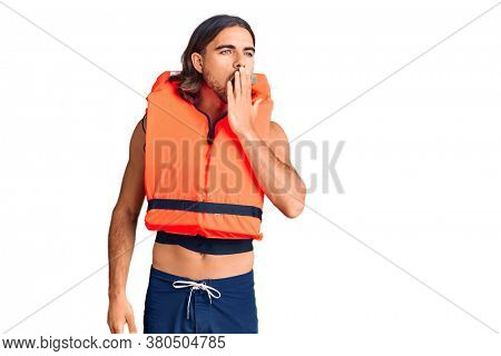 Young handsome man wearing nautical lifejacket bored yawning tired covering mouth with hand. restless and sleepiness.
