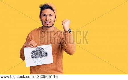 Handsome latin american young man holding rain draw annoyed and frustrated shouting with anger, yelling crazy with anger and hand raised