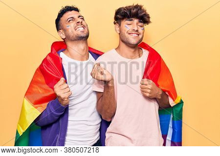 Young gay couple wearing rainbow lgbtq flag screaming proud, celebrating victory and success very excited with raised arm