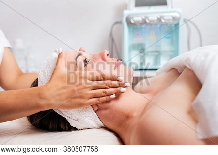 Cosmetologist Gives A Woman A Facial Massage, Cosmetic Procedure. Side View. Concept Of Cosmetology