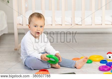 Little Boy 2 Years Old Playing Near The Crib, Early Development