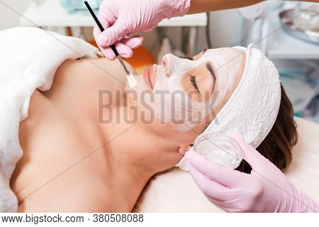 Beauty Salon. The Cosmetologist In Medical Gloves Holds A Bowl With Cosmetics, Applying A Brush Mask