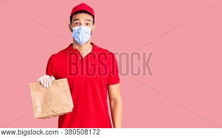 Young handsome hispanic man delivering food wearing covid-19 safety mask scared and amazed with open mouth for surprise, disbelief face
