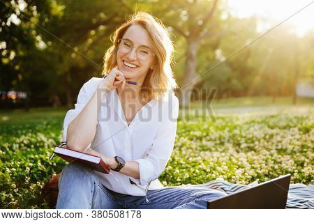 Young woman writing something in the notebook in the park.