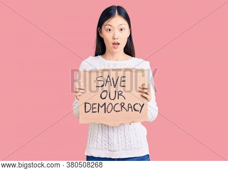 Young beautiful chinese woman holding save our democracy cardboard banner scared and amazed with open mouth for surprise, disbelief face