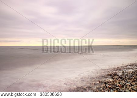 Long Exposure Of Clouds Above Smooth Ocean  Within Sunset. Line Of A Wooden Breakwater.