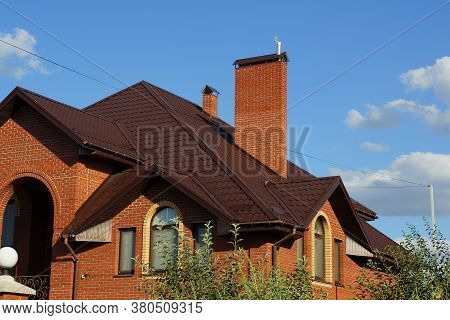 The Attic Of A Red Brick House With Windows Under A Brown Tiled Roof And A Large Chimney Against A B