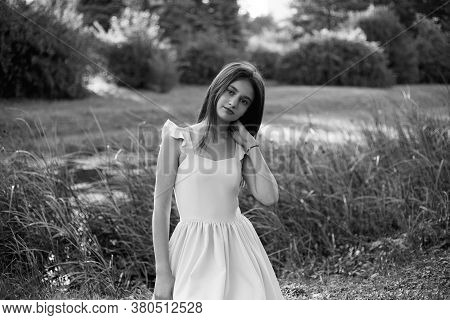 Frontal Portrait Of A Beautiful Young Girl Dressed In Dress Seated On Grass, Touching Her Neck, Look