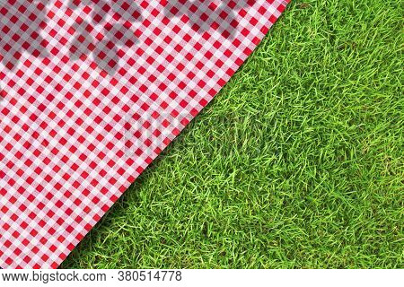 Red Checkered Table Cloth On Green Turf Or Grass From Top View.
