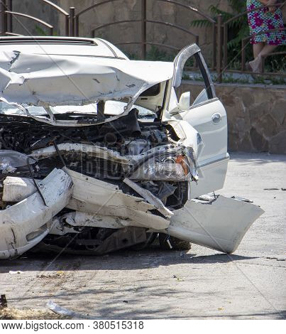 Close Up Of A White Car Wrecked During A Car Accident. Damaged Front Bumper, Engine, Headlights. Inj