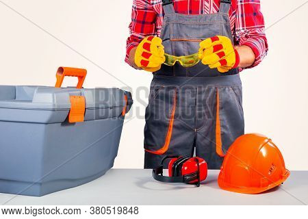 Worker Holding Goggles On Gray Background. Concept Protective Equipment And Clothing.