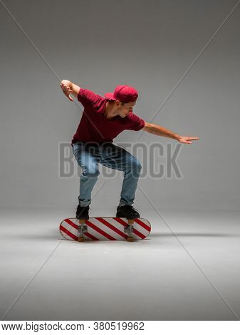Cool Guy Skateboarder Stands On Skateboard In Studio On Grey Background. Photography About Skateboar