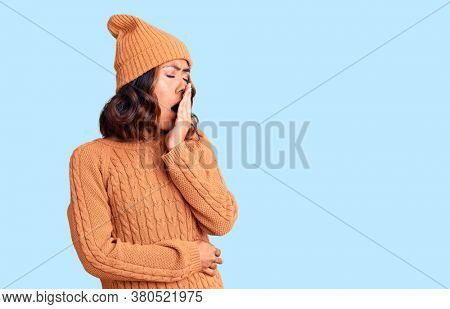 Young beautiful mixed race woman wearing wool sweater and winter hat bored yawning tired covering mouth with hand. restless and sleepiness.
