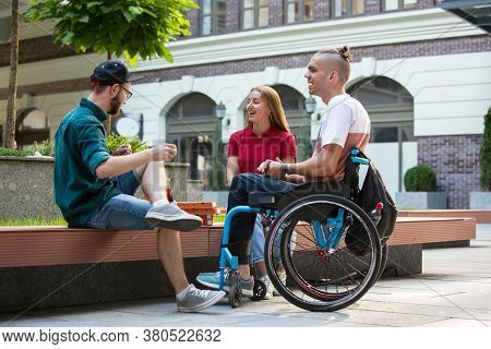 Group Of Friends Taking A Stroll On Citys Street In Summer Day. Disabled, Handicapped Man With His F