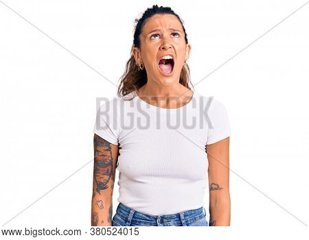 Young hispanic woman with tattoo wearing casual white tshirt angry and mad screaming frustrated and furious, shouting with anger. rage and aggressive concept.