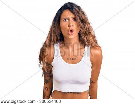 Young hispanic woman with tattoo wearing casual clothes scared and amazed with open mouth for surprise, disbelief face