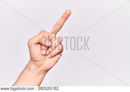 Close up of hand of young caucasian man over isolated background showing provocative and rude gesture doing fuck you symbol with middle finger