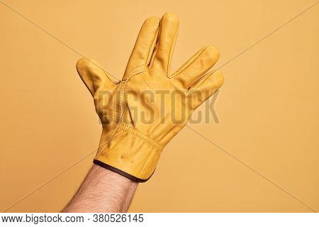 Hand of caucasian young man with gardener glove over isolated yellow background greeting doing Vulcan salute, showing back of the hand and fingers, freak culture