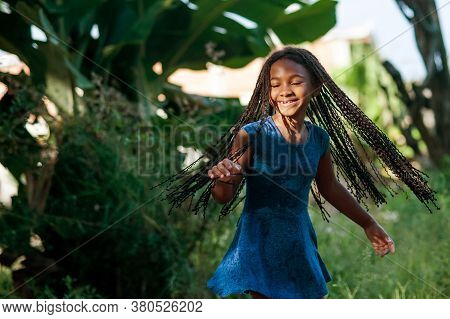 African Girl Playing And Dancing  In The Nature
