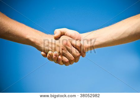 Two persons shaking hands in front of bright blue sky.